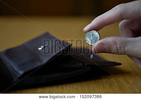 Male hand holding one Israeli Shekel (also Israeli new Sheqel, ILS or NIS ) and withdrawing that from the brown leather wallet