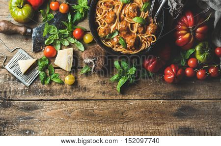 Italian pasta spaghetti with tomato sauce and meatballs in cast iron pan served with Parmesan cheese, fresh basil and colorful tomatoes over old rustic wooden background. Top view, copy space