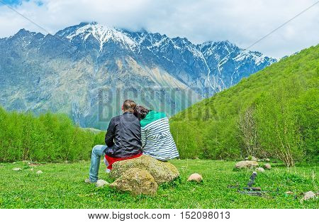 The young couple sits on boulder in the middle of the glade girl puts the head on her bofriend's shoulder Kazbegi National Park Georgia.