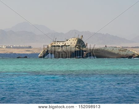 old wrecked cracked broken rust abandoned ship lays on coral reef at the Red Sea