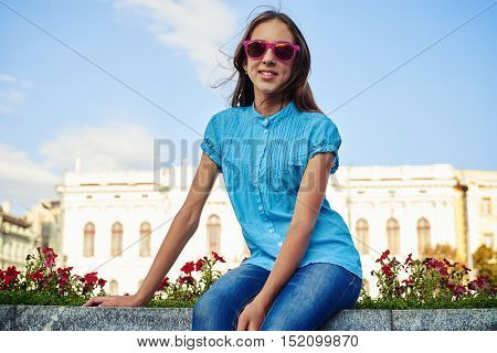 Portrait of pretty young teenage girl in pink sunglasses sitting outdoors on flowerbed