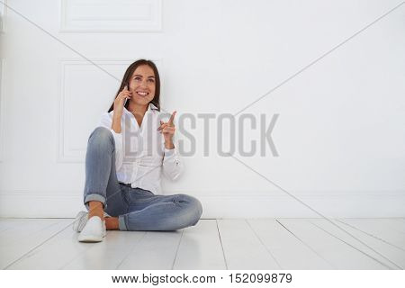 Close-up portrait of young joyous woman'??s facial emotions while talking on the smart phone