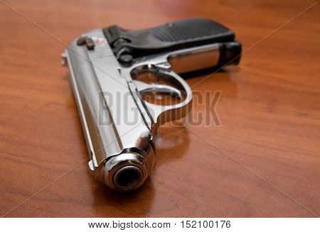 Silver pistol lyes on a brown office table