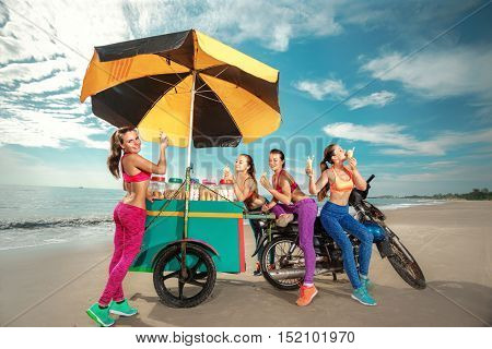 Young Women eating ice cream together next to beach vendor Ice cream, donuts and snacks on the beach
