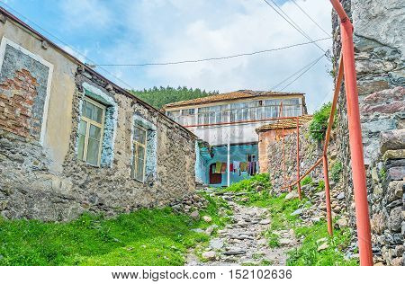 The old stone residential house on the mountain with the narrow stone path Stepantsminda Georgia.