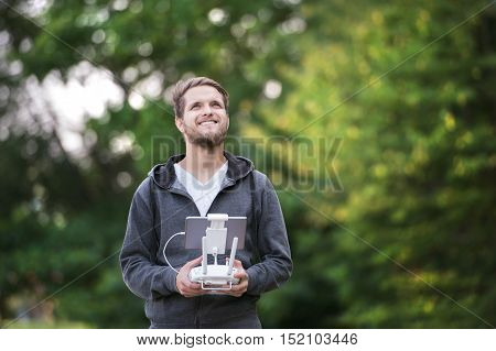 Handsome young hipster man with remote control. Green sunny nature.
