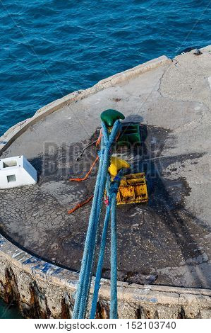 Blue ropes tied to bollards on concrete pier