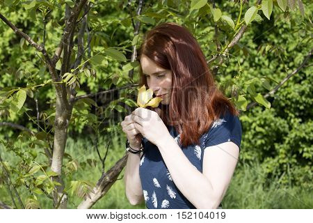 Beautiful woman with flower in her hands. Smiling face with freckles. Nice redhead girl. Portrait of young woman. Redhead woman smells yellow flower.
