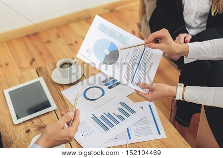 Close up of arms of colleagues analyzing document together in office