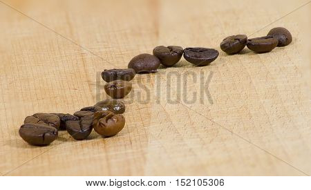 several coffee beans on a wooden surface