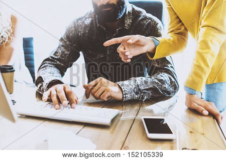 Bearded man working in a office at the computer.Female hand pointing on desktop screen.Horizontal, blurred