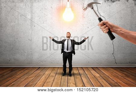 Hand holding a hammer going to break glowing bulb over businessman's head. Initiative is punishable. Killing potential. Limit the idea.