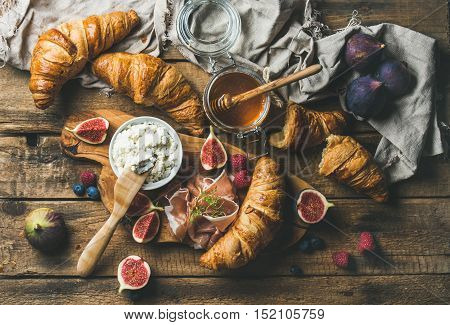 Breakfast with freshly baked croissants, ricotta cheese, figs, fresh berries, prosciutto di Parma and honey in glass jar over rustic wooden background, top view, horizontal composition