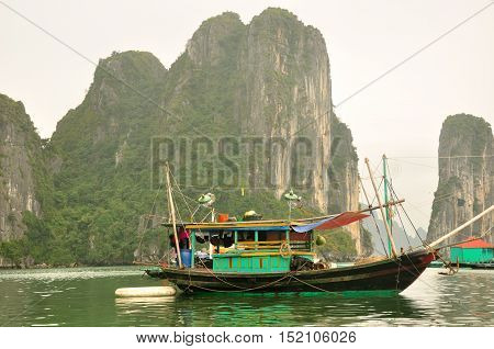 A wooden boat moored near the unique rock formations and islands within the waters of Halong Bay in Vietnam on an overcast day.