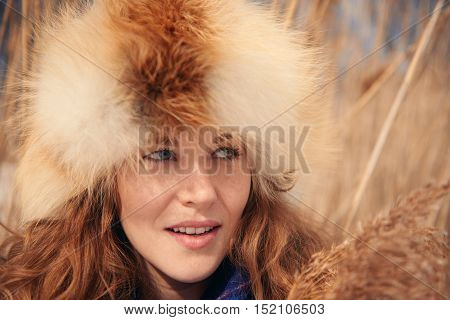 Millenial girl in long grass in a snow filled park