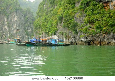 A number of wooden boats moored together in Vinh Ha Long or HaLong Bay in Vietnam on an overcast day.