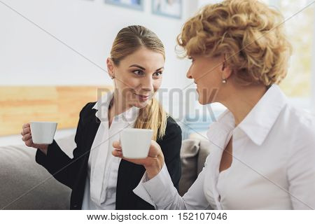 Cheerful female colleagues are gossiping on break. They are drinking coffee and smiling