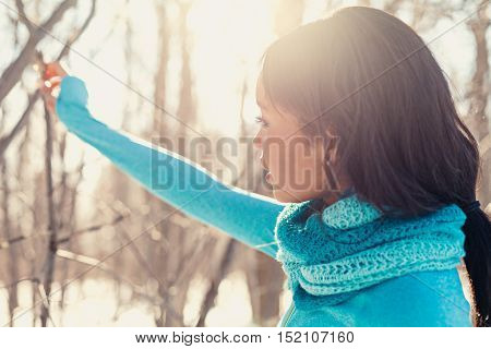 African-American millenial touching a tree in wintertime in a snow filled park