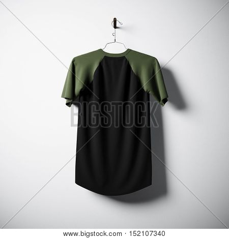 Blank black and green cotton tshirt hanging in center of empty concrete wall. Clear label mockup with highly detailed textured materials. Square. Back side view. 3D rendering