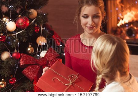 Mother giving daughter present at Christmas Eve