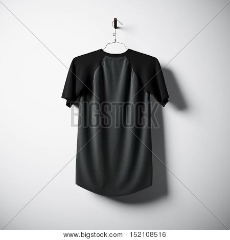 Blank cotton tshirt of black and gray colors hanging in center of empty concrete wall. Clear label mockup with highly detailed textured materials. Square. Back side view. 3D rendering
