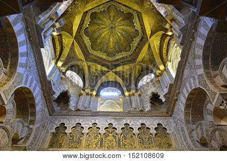 Cordoba, Spain - July 18, 2015. Ornate ceiling above the mihrab in the Mezquita of Cordoba, with paintings and inscriptions. The entire mihrab portal incorporates 1600kg of gold mosaic cubes, a gift from the Christian emperor of Byzantium.
