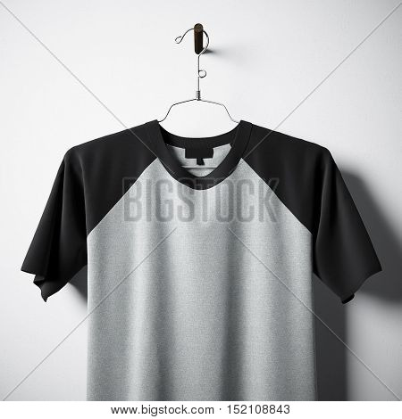 Closeup of blank cotton tshirt of gray and black colors hanging in center of empty concrete wall. Clear label mockup with highly detailed texture materials. Square. Front side view. 3D rendering