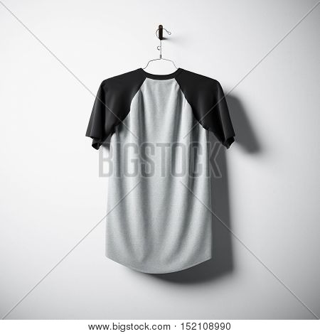 Blank cotton tshirt of gray and black colors hanging in center empty concrete wall. Clear label mockup with highly detailed texture materials. Square. Back side view. 3D rendering