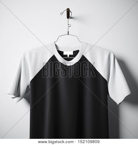 Closeup of blank cotton tshirt of white and black colors hanging in center empty concrete wall. Clear label mockup with highly detailed textured materials. Square. Front side view. 3D rendering
