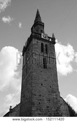 An external view of a stone church clock tower in Cupar