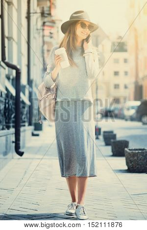 Listen to me. Joyful content young beautiful woman talking on smart phone and drinking coffee while walking in the street
