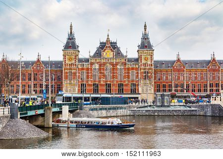 Amsterdam, Netherlands - April 2, 2016: Railway station, cruise boat with tourists and canal view in Amsterdam, Netherlands