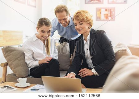 Successful colleagues are looking at laptop with satisfaction. They are sitting on couch and smiling
