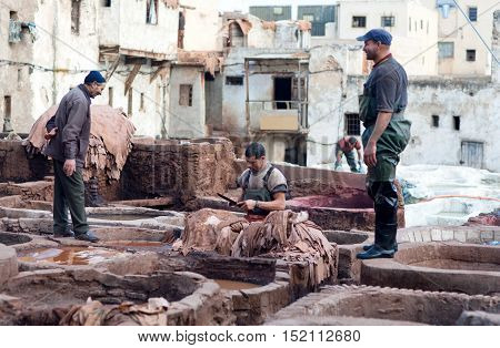 FEZ, MOROCCO - JANUARY 4, 2014: Men working hard in the tannery souk. The tannery souk of weavers is the most visited part of the 2000 years old city.