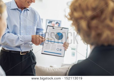 Professional businessman is sharing his idea with colleagues and smiling. He is standing and pointing at document. Women are listening to him attentively