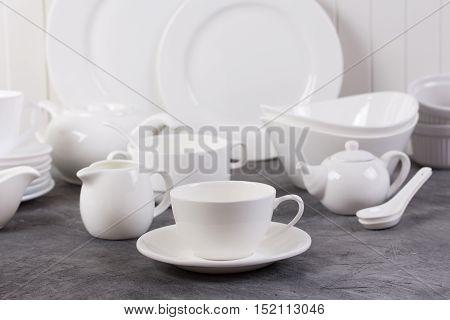 Set of white crockery and kitchen utensils on grey background
