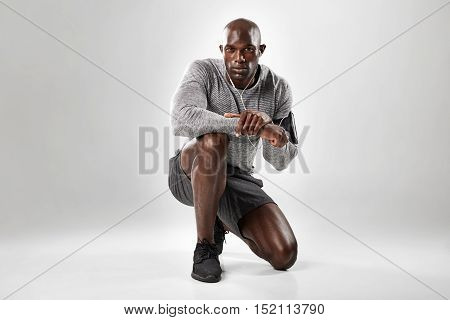 Fit Young African Man Kneeling On Grey Background