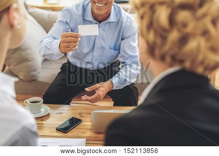 Confident businessman is showing his visiting card to women and smiling. He is sitting on sofa