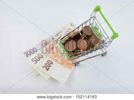 Glossy and colorful coins with banknotes in the shoping cart. Bank product. Financial item. Isolated background