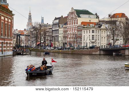 Amsterdam, Netherlands - April 2, 2016: Traditional old buildings, canal and boat with tourists in Amsterdam, Netherlands