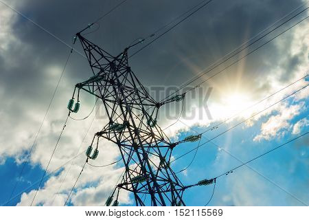 A high voltage power pylons against blue sky. The photo shows a blue sky with cloud through which the sun shines