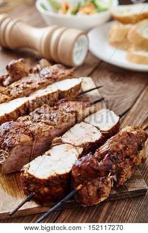 Delicious juicy skewered meat or shish kebabs on skewers of pork tenderloin in marinade of paprika, garlic, thyme and orange peel on wooden cutting board. Fragrant and spicy dish. Selective focus