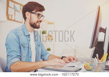Good work. Smiling young handsome programmer wearing glasses and working on a computer while sitting in an office.