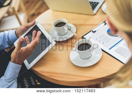 Close up of team hands working in cooperation. Businessman is holding tablet. Woman is sitting at table and reading document