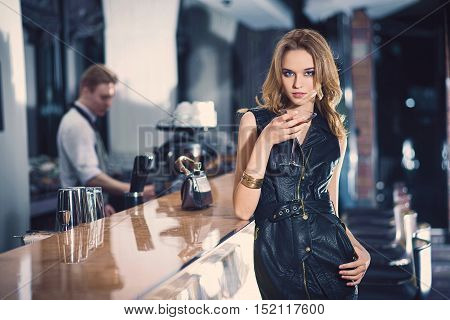 romantic portrait of elegand blond woman , smiling on side sitting and waiting for someone in a luxury bar