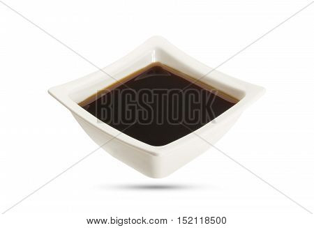 Bowl with soy sauce isolated on black background