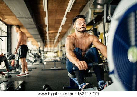 Determined young handsome bodybuilder rowing in gym