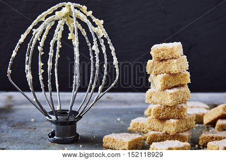 Delicious homemade cookies made from semolina. Crumbly, delicate texture, the sugar crust on top. A little sweetness to the tea on gray background. Attachment for mixer behind. Selective focus