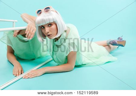 Cute young woman in blonde wig lying near the mirror