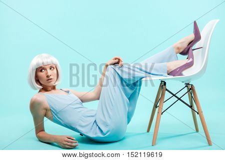 Attrative blonde young woman lying and posing with chair